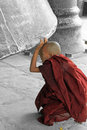Novice monk looking under mingun bell a peering the large with a rose petal by his foot Royalty Free Stock Images
