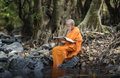 Novice monk reading a book in the streams Royalty Free Stock Photo