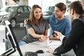 Now her dream comes true car salesman giving the key of the new to young attractive owners Stock Photo