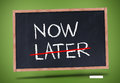 Now and later written on blackboard against green background Stock Image