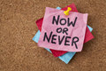 Now or never motivational reminder on a green sticky note Royalty Free Stock Images