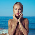 Nude blonde at the sea elegant with body in sand of Royalty Free Stock Image