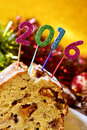 Number as the new year on a fruitcake closeup of four glittering numbers of different colors forming topping with some tinsel and Stock Photos