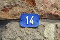 Number blue house fourteen sign at stone wall Royalty Free Stock Photography