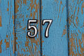 Number 57 on blue wooden wall with peeling paint
