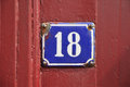 Number eighteen house sign on red wooden panel Royalty Free Stock Image