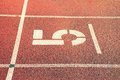 Number five. Big white track number on red rubber racetrack. Gentle textured running racetracks in athletic stadium. Royalty Free Stock Photo