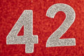 Number forty-two silver color over a red background. Anniversary