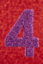 Number four purple color over a red background. Anniversary.
