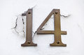 Number fourteen on cracked wall brass figures for the screwed to a plastered which is cracking outside pillar of a building in Royalty Free Stock Photo