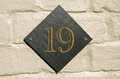 Number nineteen etched in gold onto a diamond shaped piece of slate outside wall of a house viewed from public pavement Stock Photo