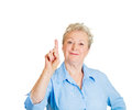 Number one sign closeup portrait of senior mature smiling woman pointing with index finger hand upwards got idea isolated white Royalty Free Stock Image
