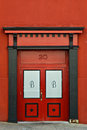 Number red double door street over doors with the letter b on each framed by black and arch and columns Stock Images