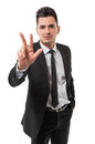 Number three in business businessman wearing a black suit and black tie isolated on white background showing with his right hand Royalty Free Stock Images