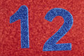 Number twelve blue color over a red background. Anniversary.