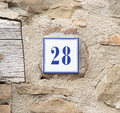 Number twenty eight on the grey stone wall Royalty Free Stock Photo
