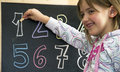 Numbers girl write on the blackboard Stock Photography