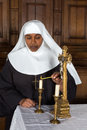 Nun and altar standing at the lighting a candle Royalty Free Stock Images