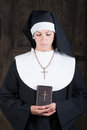 Nun with bible looking down Stock Image