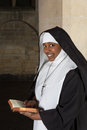 Nun with bible smiling reading the in a medieval church Stock Photos