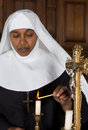Nun lighting a candle mature on the altar of medieval church Stock Photos