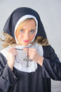 Nun putting on Christian cross Stock Image
