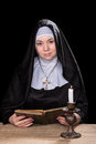 Nun at a table with book beautiful sitting wooden an open in his hands worn on black background Royalty Free Stock Photos