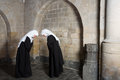 Nuns greeting two eachother inside a medieval abbey Royalty Free Stock Photography