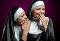 Nuns whispering a secret to another nun young attractive Stock Image