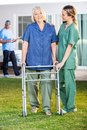 Nurse assisting senior woman to walk with zimmer female women frame in lawn at nursing home Royalty Free Stock Images
