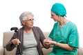 Nurse comforting old woman tending an disabled senior lady with crutch hand in hand with a carer isolated on white Royalty Free Stock Images
