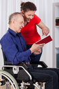 Nurse and disabled man reading book Royalty Free Stock Photo