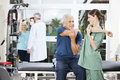Nurse guiding senior patient in arm exercise at rehab center smiling female fitness Stock Photos