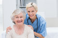 Nurse with hands on senior patients shoulders in clinic portrait of friendly Stock Images