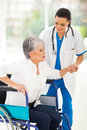 Nurse helping senior beautiful medical woman on wheelchair Stock Photos