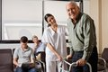 Nurse helping senior patient with walker portrait of men being assisted by female to walk zimmer frame people sitting in Stock Images