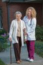 Nurse Helping Senior Walking with Cane Outdoor Stock Image