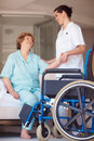 Nurse helping a senior woman onto a wheelchair Royalty Free Stock Image