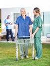 Nurse helping senior woman to use walking frame in female women lawn with caretaker background at nursing home Royalty Free Stock Image