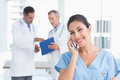 Nurse phoning while her colleagues working in medical office Stock Photography