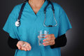 Nurse With Pills and Glass of Water Royalty Free Stock Images