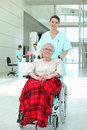 Nurse pushing a wheelchair Royalty Free Stock Image