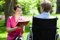 Nurse reading next to disabled woman Royalty Free Stock Photo