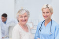 Nurse and senior patient smiling in clinic portrait of Stock Photos