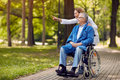 Nurse showing something to elderly man on wheelchair