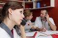 Nurse staff is phoning busy sitting on a white table Royalty Free Stock Image