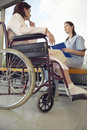 Nurse talking to patient in wheelchair low angle view of a young hospital Royalty Free Stock Image