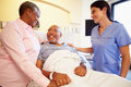 Nurse talking to senior couple in hospital room holding hands smiling Royalty Free Stock Images