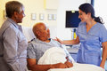 Nurse talking to senior couple in hospital room looking at each other smiling Royalty Free Stock Photos
