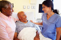 Nurse talking to senior couple in hospital room putting hand on shoulder reassuring them Royalty Free Stock Image